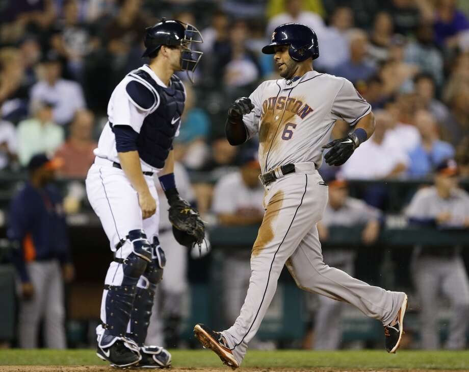 Jonathan Villar, right, scores past Mariners catcher Mike Zunino. Photo: Ted S. Warren, Associated Press