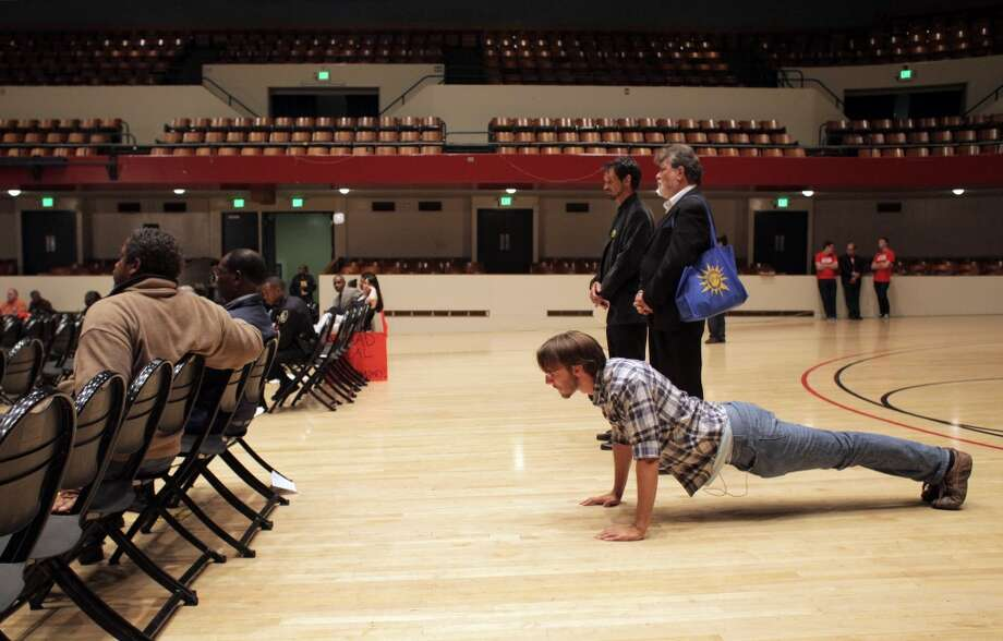 Richmond resident Zach Wear does a few pushups to stay awake during public comment on the eminent domain measure during a city council meeting on Tuesday, September 10, 2013, in Richmond, Calif. Photo: Carlos Avila Gonzalez, The Chronicle
