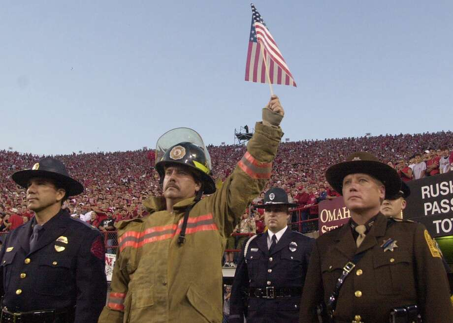 An unidentified fire fighter holds a flag high during the opening ceremony of the Nebraska-Rice University football game held at Memorial Stadium in Lincoln, Neb., Thursday Sept. 20, 2001.  (AP Photo/Dave Weaver) Photo: DAVE WEAVER, ASSOCIATED PRESS / AP2001