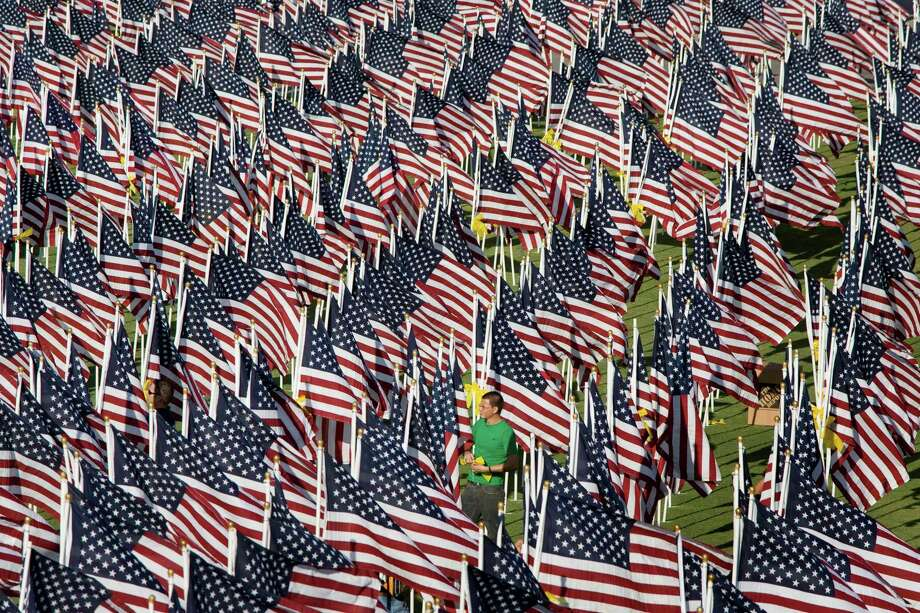 A volunteer ties yellow ribbons to an American flag pole as part of the Healing Field Memorial at Tempe Beach Park in Tempe, Ariz. on Wednesday Sept. 10, 2008. Over 3,000 flags are on display in memory of the victims of the Sept. 11, 2001 attack.  (AP Photo//The Arizona Republic, Mark Henle) Photo: Mark Henle, AP / The Arizona Republic