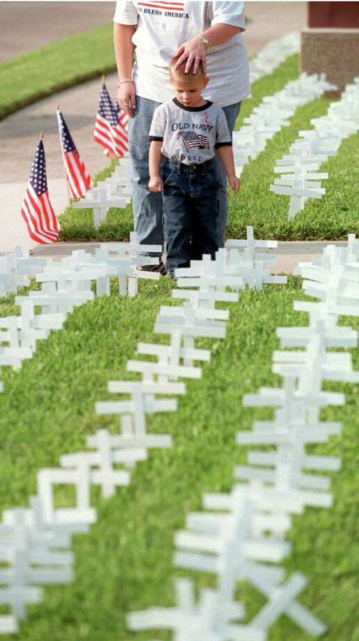 Reagan Dawson, 3, and his mother, Jaclyn (CQ) Dawson, look at 3000 crosses placed outside the Uvalde Baptist Church, 901 Uvalde, to honor the people who died 9/11. They are church members and stopped to look at the display on their way into an evening 9/11 remembrance service at the church on Wednesday, Sept. 11, 2002.  (Melissa Phillip/Chronicle) Photo: Melissa Phillip, Houston Chronicle / Houston Chronicle