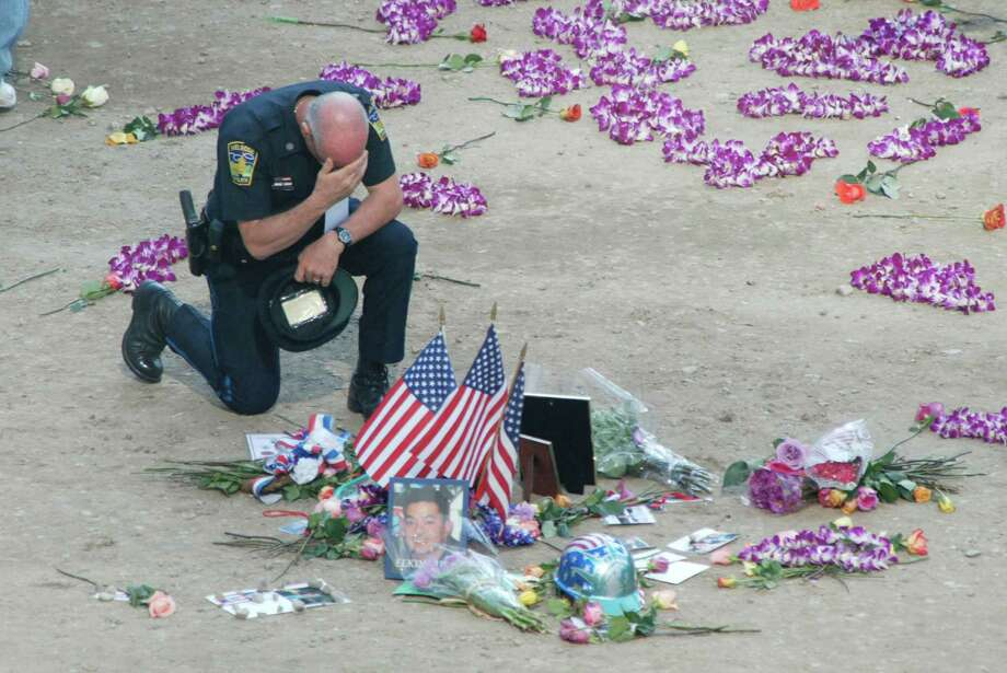 An NYPD officer mourns at the World Trade Center memorial service at Ground Zero September 11, 2002 in New York City.  (Photo by Jason Szenes-Pool/Getty Images) Photo: Getty Images / Getty Images North America
