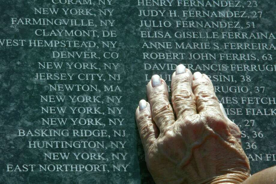 A woman puts her hand on the names of those killed in the terrorist attacks on Sept. 11th, inscribed in granite on a memorial in Montclair, N.J., Thursday, Sept. 11, 2003. On the second anniversary of the attacks, some people paid tribute to those who died at the memorial in Essex County, N.J. (Ozier Muhammad/The New York Times) Photo: OZIER MUHAMMAD, NYT / NYTNS