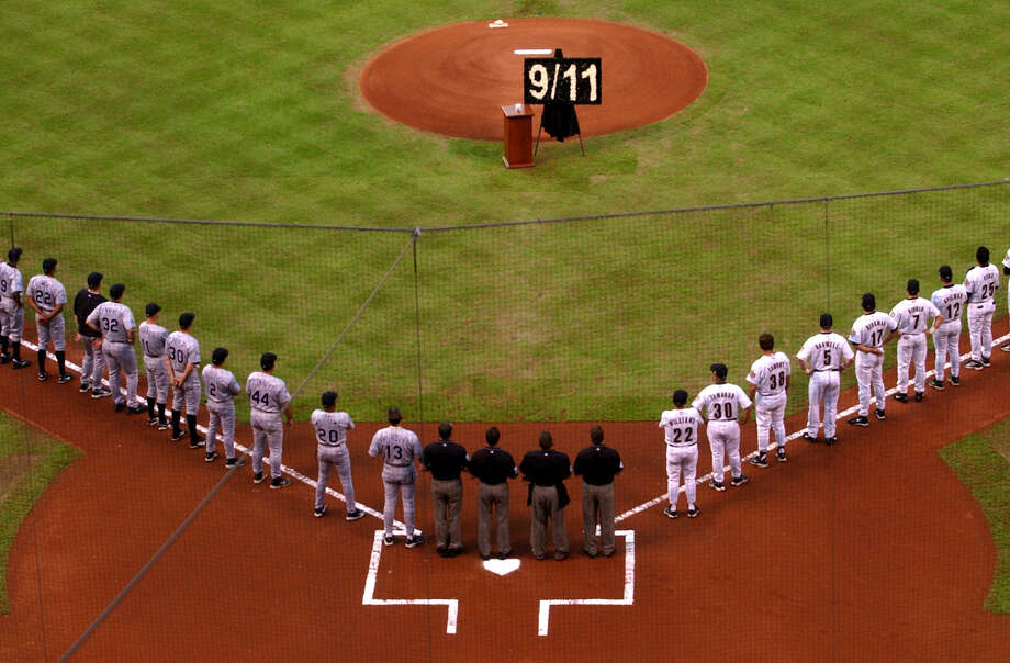 The Houston Astros and Colorado Rockies line up with a 9/11 wreath on the pitchers mound, during the 9/11 pregame ceremony before the start of the Houston Astros-Colorado Rockies game at Minute Maid Park, Wednesday evening. (Karen Warren/Houston Chronicle) Photo: KAREN WARREN, HOUSTON CHRONICLE / HOUSTON CHRONICLE