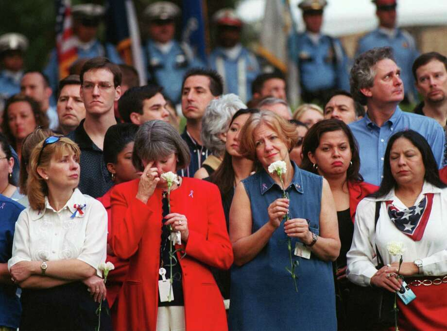 "Emotions were high as Houstonians holds back tears Wednesday, Sept. 11, 2002 during a an early morning ceremony in Houston as an observance of the one year anniversary of the 9-11 attacks. ""Houston Remembers"" Houston Mayor Lee P. Brown lead the city in  ceremony at City Hall, Thousands of carnations were dropped onto the City Hall reflection pool, honoring the dead, which was highlighted by a red, white and blue wreath, eight feet in diameter.  Photo by Carlos Antonio Rios/ Chronicle. Photo: Carlos Antonio Rios, Houston Chronicle / Houston Chronicle"