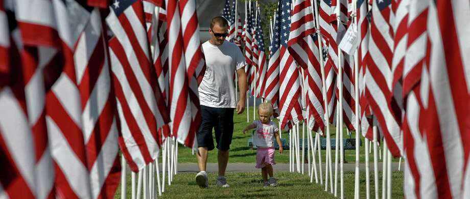 Chris Kayder and his daughter, Cadence, walk among the flags honoring those who died in the 9/11 attacks Monday, Sept 10, 2012 at the healing field in Tempe, Ariz. Volunteers set up 2,996 American flags Sunday morning for the annual Healing Field memorial in Tempe that honors those who died in the Sept. 11 terrorist attacks. Each flag represents a person who lost his or her life in the attacks on the World Trade Center in New York City, the Pentagon in Washington, D.C., and Pennsylvania in 2001, and are marked with placards with the name of victims, information about them and where they died. (AP Photo/Matt York) Photo: Matt York, Associated Press / AP