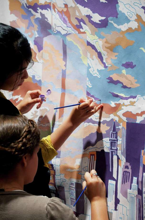 Jessica Huynh, top, and Alana Roecker brush in the colors of a paint-by-number canvas of the original World Trade Center towers, at a news conference, Monday, Sept. 10, 2012 in New York. On the eve of the Sept. 11 anniversary, the faces and recorded voices of those who died have been unveiled as part of the future 9/11 Memorial Museum. (AP Photo/Mark Lennihan) Photo: Mark Lennihan, Associated Press / AP