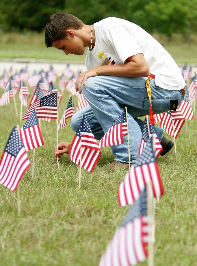 Trent Kirkpatrick, 17, a senior, straightens one of the flags that he put up at the 9/11 flag memorial (3,000 flags total to represent the 2,996 people killed in the attacks)  set up in front of Klein Oak High School by members of the Klein Oak Young Conservatives group,  Friday, Sept. 11, 2009, in Houston. Kirkpatrick, the Vice President of the Young Conservatives,  started fundraising for the flags a month ago, and with the help of a few friends, set up the flags last night,   in commemoration of the terrorist attacks on Sept. 11, 2001. (Karen Warren/Chronicle) Photo: Karen Warren, Houston Chronicle / Houston Chronicle