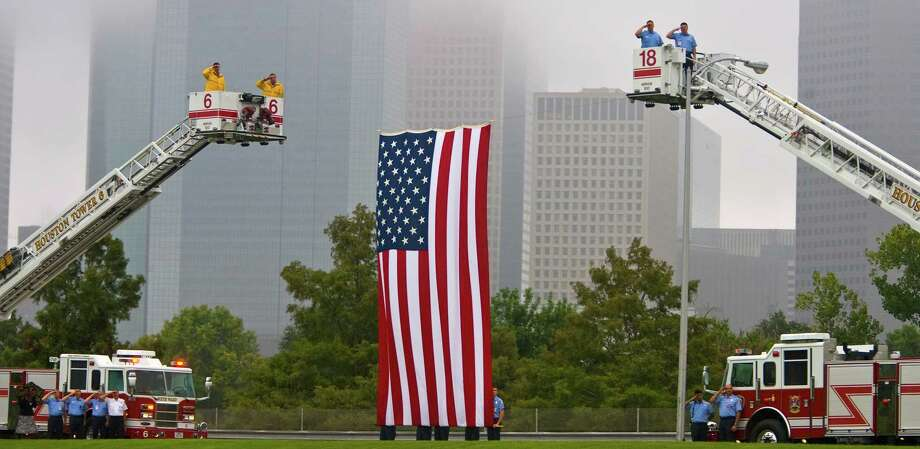 "Houston Firefighters salute during the playing of ""Taps"" as they stand their post near a giant American flag, hung between Ladder 6 and Ladder 18, during the 9/11 Memorial ceremony held at the Houston Police Memorial,  Friday, Sept. 11, 2009, in Houston,  by the Houston Police and Houston Fire Departments,  in commemoration of the terrorist attacks on Sept. 11, 2001. (Karen Warren/Chronicle) Photo: Karen Warren, Houston Chronicle / Houston Chronicle"