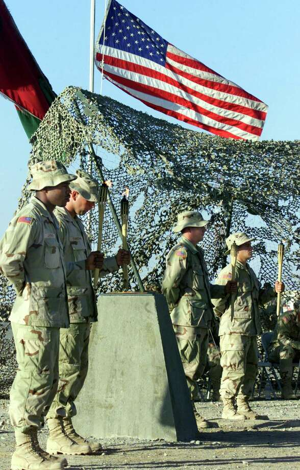 Four U.S. Soldiers at Kandahar Airbase hold torches symbolizing the four planes used in last years Sept. 11 terrorist attacks in the United States Wednesday Sept. 11, 2002 outside Kandahar, Afghanistan.  Soldiers at bases around Afghanistan said that the memories of last year's attacks gives them a renewed sense of purpose.(AP Photo/Ed Wray) Photo: ED WRAY, AP / AP