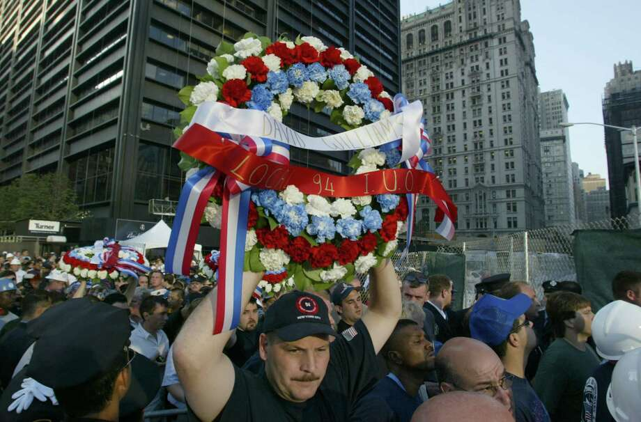 A union worker carries a memorial wreath above his head as he makes his way through the crowd to the 9/11 commemoration ceremony at Ground Zero in New York City Wednesday morning September 11, 2002. (D. Fahleson / Houston Chronicle) Photo: D. Fahleson, Houston Chronicle / Houston Chronicle