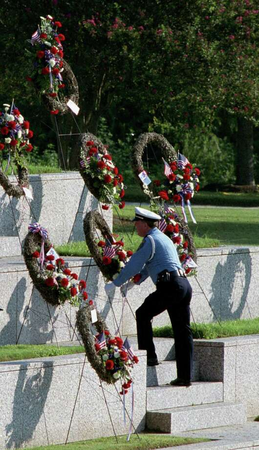 Houston police officer W.E. Johnson with the Honor Guard lays a wreath at the Police Memorial in Houston. 25 wreaths were put up by Allied Florists of Houston in honor of the Houston Police Departments brethren who died in NYC on 9-11. Photo by Carlos Antonio Rios. Photo: Carlos Antonio Rios, Houston Chronicle / Houston Chronicle
