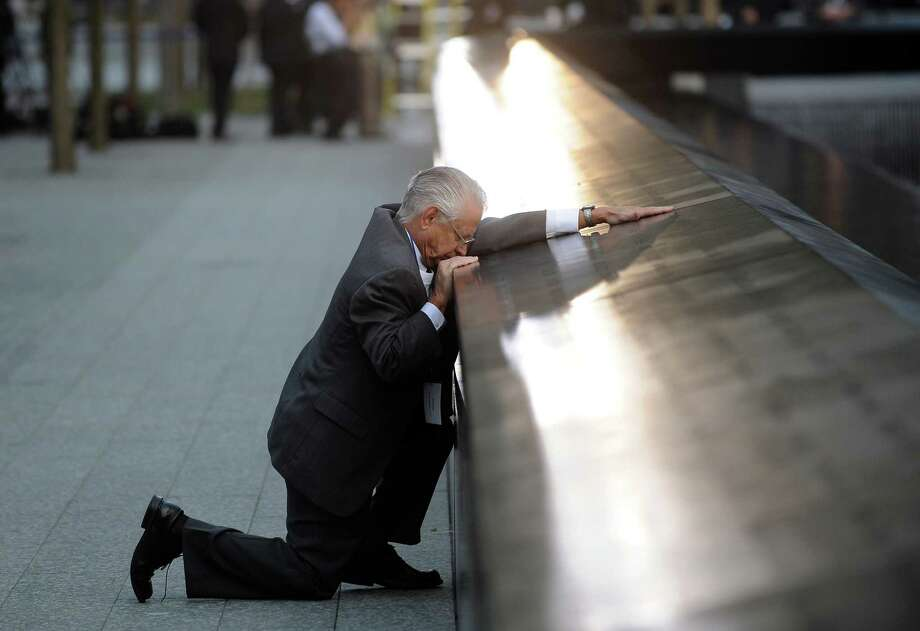 Robert Peraza, who lost his son Robert David Peraza in the attacks at the World Trade Center, pauses at his son's name at the North Pool of the 9/11 Memorial before the 10th anniversary ceremony at the site, Sunday Sept. 11, 2011, in New York. (AP Photo/Justin Lane, Pool) Photo: Justin Lane, Associated Press / Copyright 2011 The Associated Press. All rights reserved. This material may not be published, broadcast, rewritten or redistribu