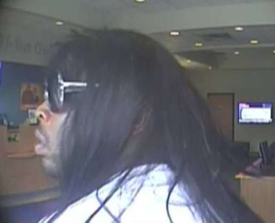 The FBI is looking for this suspect in connection with the robbery this week of of a credit union in northwest Houston. He is described as a black male, about 6 feet tall with a heavy build, and was wearing a white T-shirt and khaki-colored cargo shorts, a shoulder-length black wig and sunglasses. Photo: Bankrobbed0911