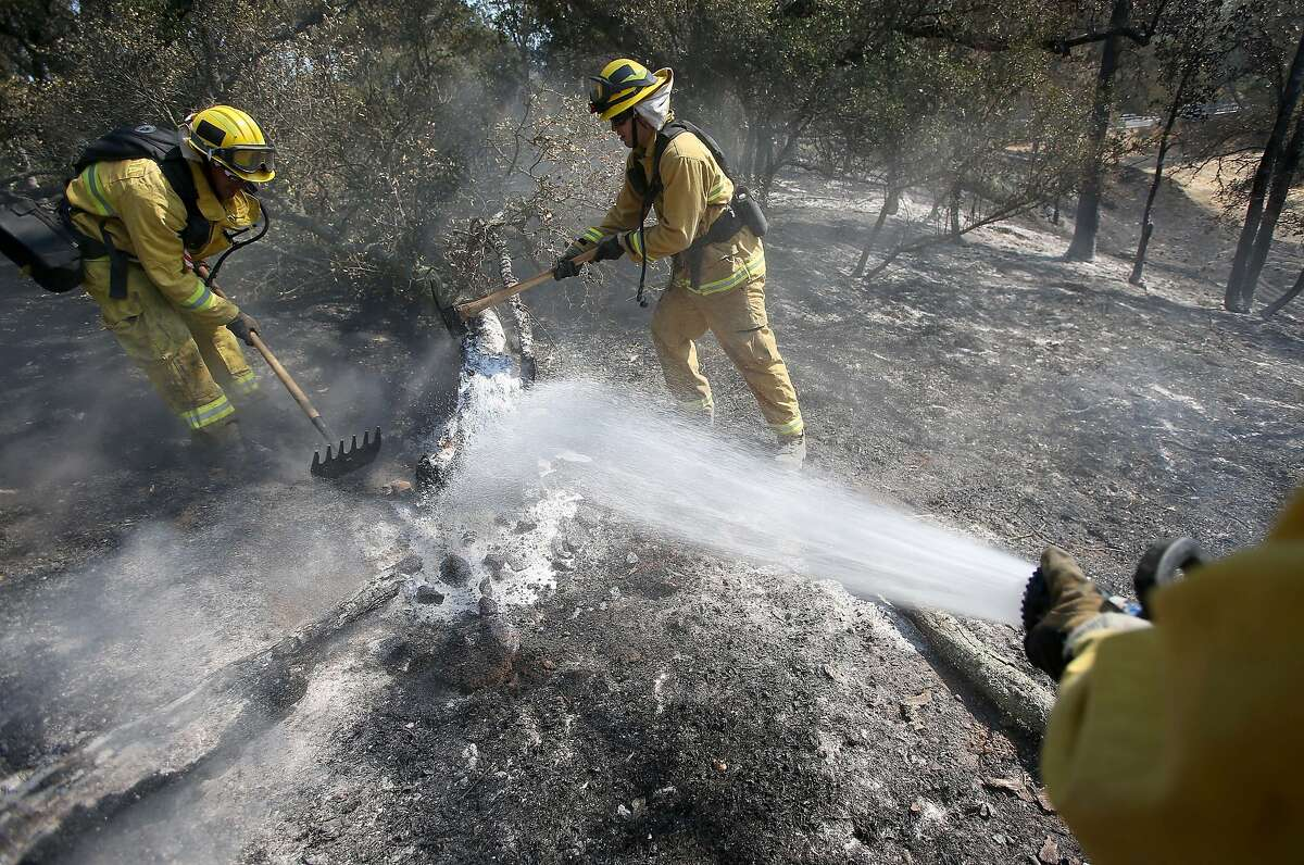 Santa Clara County firefighters Nick Nanez, left, and Mike Hughes help put out hot spots at the Morgan Fire along Morgan Territory Road in unincorporated Contra Costa County near Mount Diablo and Clayton, Calif., on Tuesday, Sept. 10, 2013. The fire began on Sunday, Sept. 8, and by Tuesday, more than 3,200 acres had burned and containment was at 45 percent. (AP Photo/The Contra Costa Times, Jane Tyska)