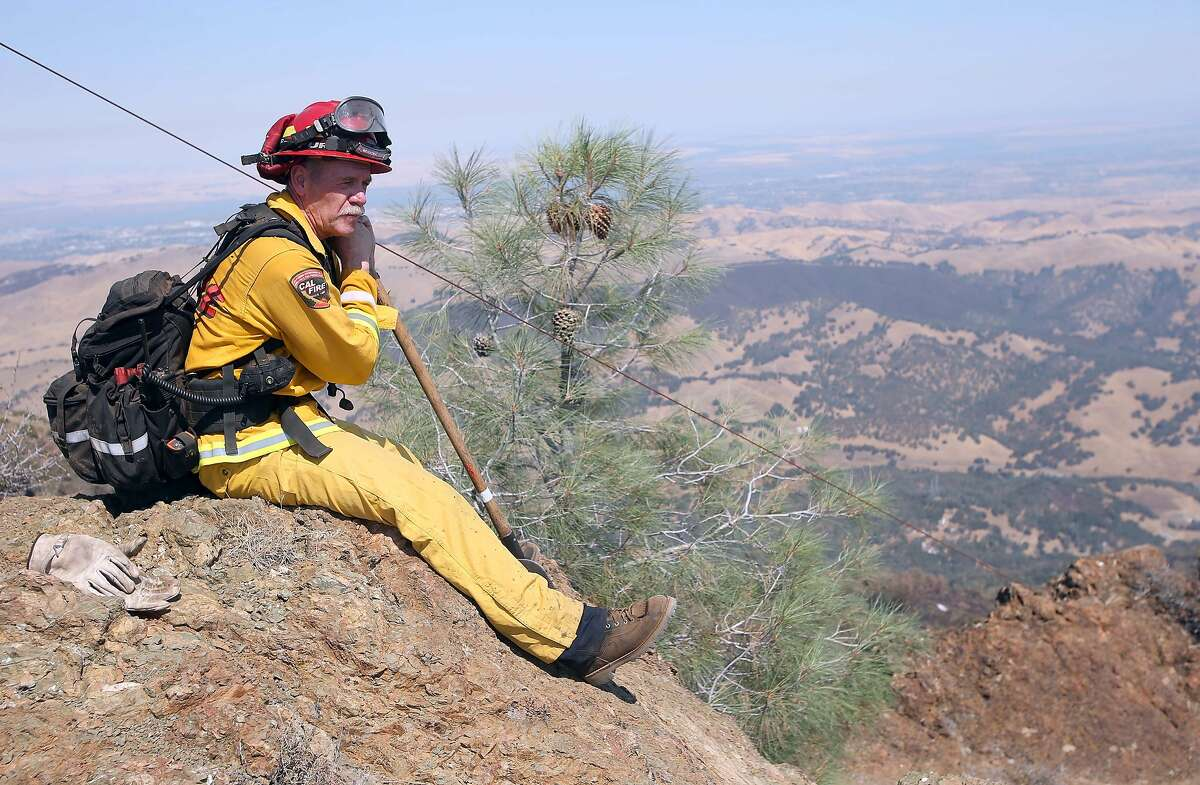 Delta Camp firefighter Ken Pridmore scans for smoke and hot spots on the north peak of Mount Diablo in unincorporated Contra Costa County near Clayton, Calif., on Tuesday, Sept. 10, 2013. The Morgan Fire began on Sept. 8, and by Tuesday more than 3,200 acres had burned and containment was at 45 percent. (AP Photo/The Contra Costa Times, Jane Tyska)