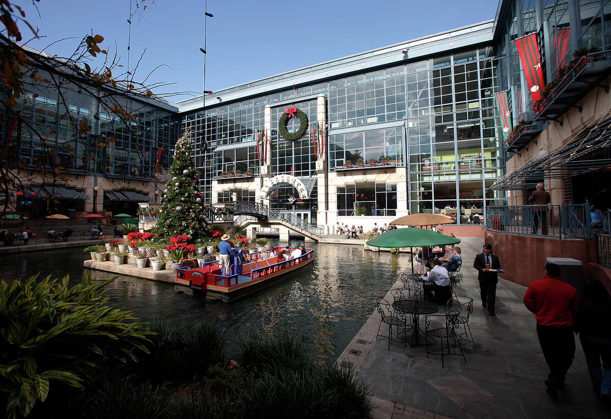 A river barge takes visitors on a tour along the River Walk near the RiverCenter Mall as patrons stroll and have lunch along the sidewalks on Friday, Dec. 10, 2010. Kin Man Hui/kmhui@express-news.net