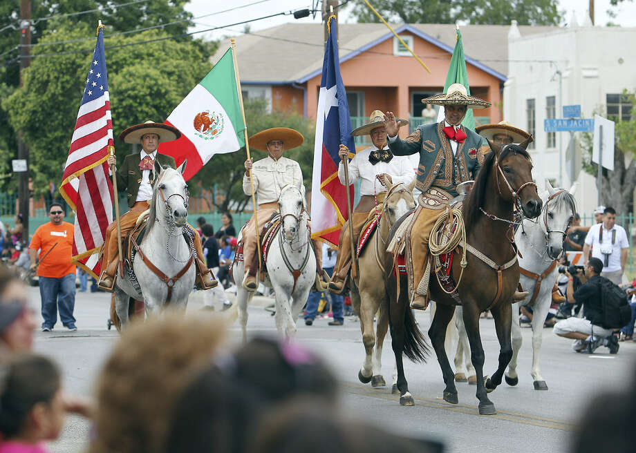 Caballeros carrying the U.S., Texas and Mexico flags stroll down the street at the 31st annual 16 de Septiembre Parade in 2012. The annual event kicks off Hispanic Heritage Month. Photo: San Antonio Express-News File Photo