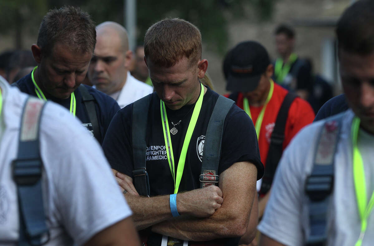 San Antonio firefighter Cody Davenport (center) bows his head at the Tower of the Americas early Wednesday September 11, 2013 before the San Antonio 110 9/11 Memorial Climb.