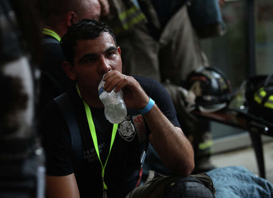 San Antonio firefighter Omar Mercado hydrates at the Tower of the Americas Wednesday September 11, 2013 after the San Antonio 110 9/11 Memorial Climb.  Photo: JOHN DAVENPORT, SAN ANTONIO EXPRESS-NEWS / ©San Antonio Express-News/Photo may be sold to the public