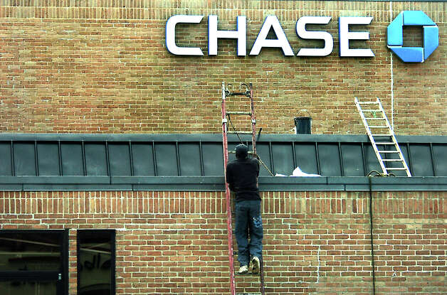 A worker climbes a ladder to repair roof damage at Chase Bank in Beaumont, TX, Friday, September 14,  2007. Hurricane Humberto roared into the area Thursday with high winds and heavy showers. (Beaumont Enterprise, Tammy McKinley) Photo: TAMMY MCKINLEY