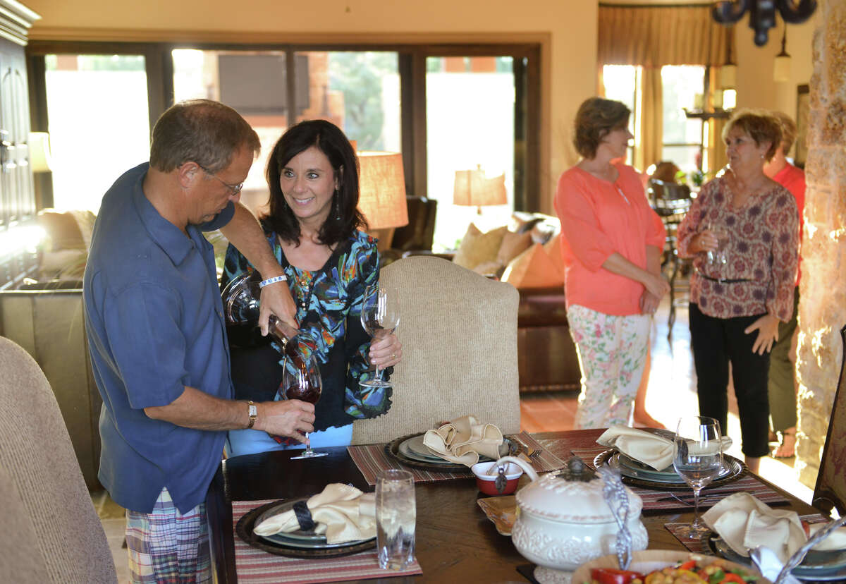Randy Frazee and his wife Rozanne pour wine for a recent dinner with family and neighbors.