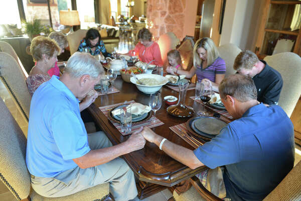 Family and neighbors join hands to pray before dinner at the Frazee home.