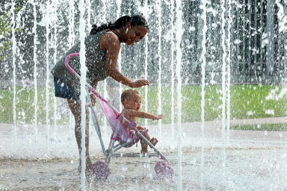 MaryJo Owusu of Troy and her granddaughter 1-year-old Aundraia Mann cool off in the fountains at UAlbany on Wednesday Sept. 11, 2013 in Albany, N.Y. (Michael P. Farrell/Times Union) Photo: Michael P. Farrell / 00023837A