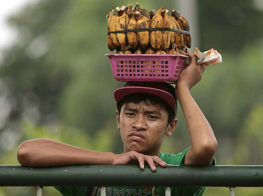 Yes, we have no unboiled bananas: Selling boiled bananas in Quezon city, Philippines, apparently isn't his idea of fulfilling work. Photo: Aaron Favila, Associated Press