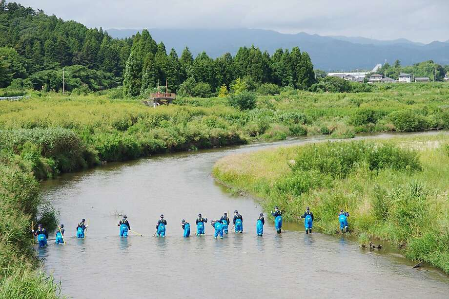 Police search a riverfor people still missing two and half years after a massive earthquake and tsunami 