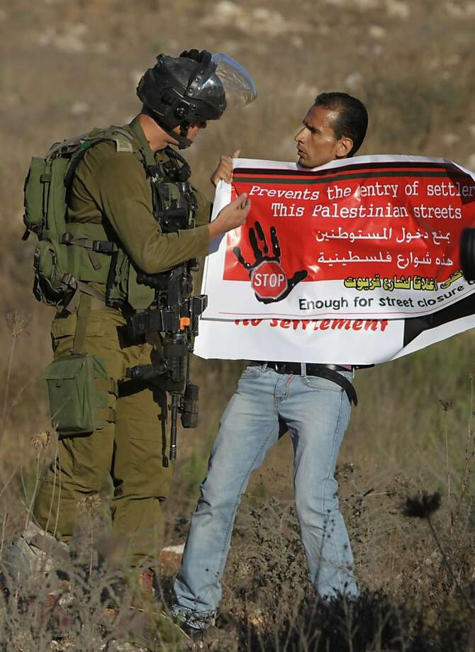 For starters, you have a syntax error and subject-verb agreement problem:An Israeli soldier argues with a Palestinian 