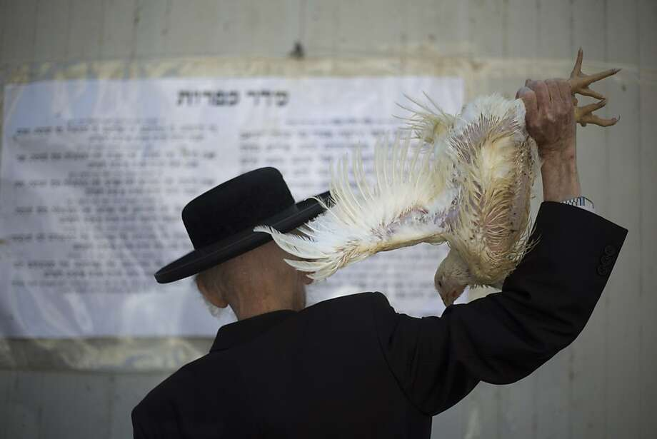 Winging it before Yom Kippur:An ultra-Orthodox Jewish man swings a chicken over his head as part of the Kaparot ritual in Bnei Brak, Israel. Jews believe the ritual, performed before the Day of Atonement, Yom Kippur, transfers 