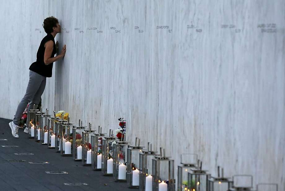 A visitor kisses a name on the wall containing the 40 names of the crew and passengers of Flight 93 at the 