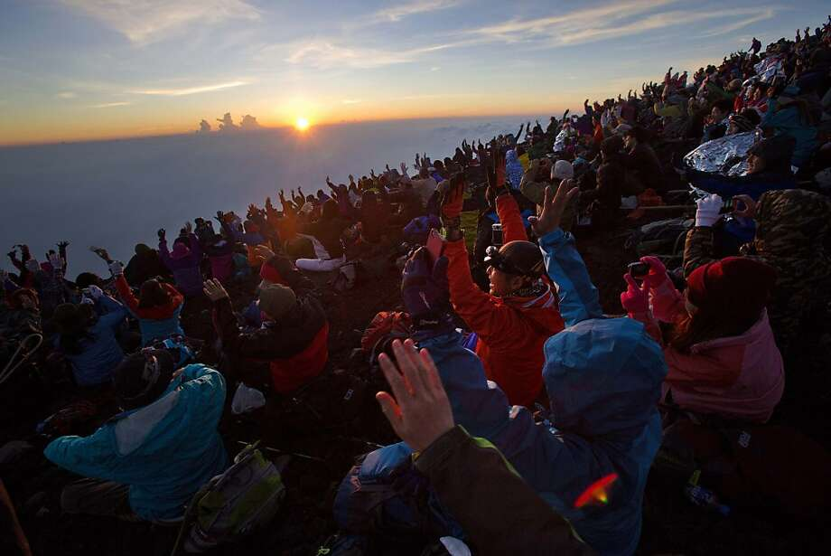 Thousands of hikers cheer from the summit of Mount Fuji in Japan as the sun rises on Aug. 11, 2013. Photo: David Guttenfelder, Associated Press
