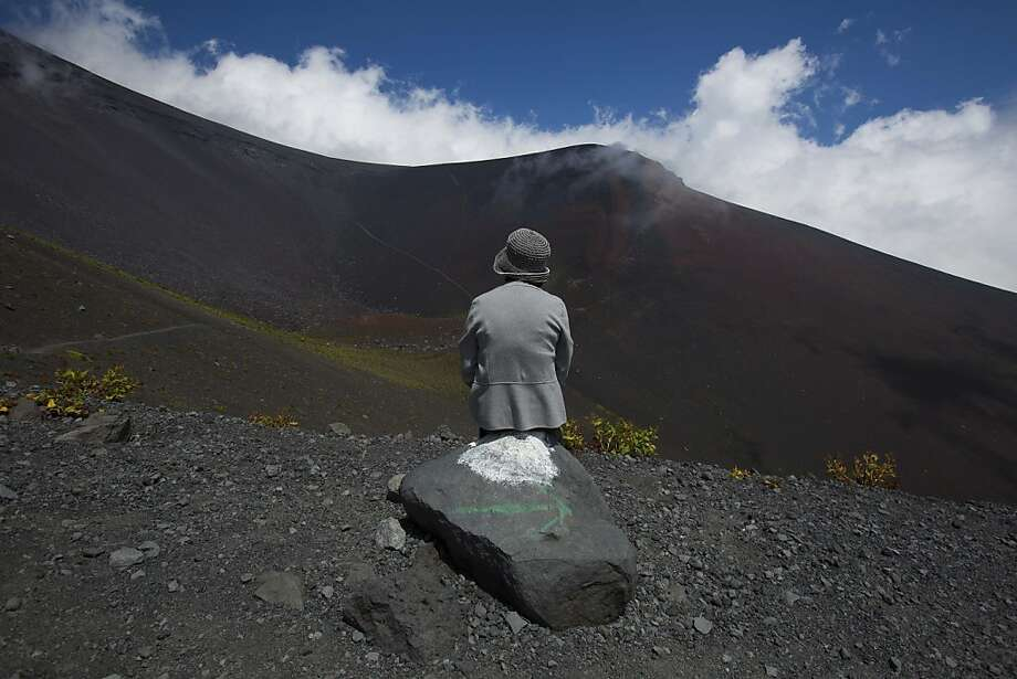 A Japanese woman sits on a rock overlooking a crater on Mount Fuji in Japan on Aug. 29, 2013. Photo: David Guttenfelder, Associated Press