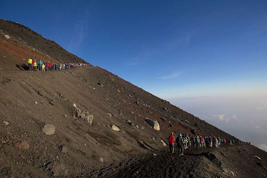 Hikers make their way down from the summit of Mount Fuji after watching the sunrise from the topon Aug. 11, 2013. Photo: David Guttenfelder, Associated Press