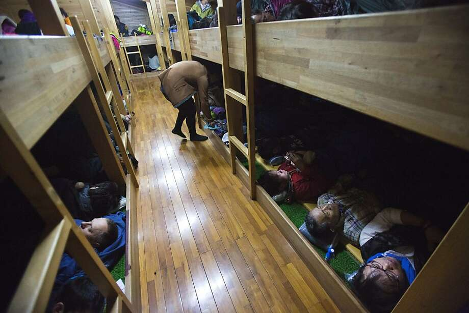 Hikers are packed into sleeping rows at a rest station before the summit of Mount Fuji in Japan onSaturday, Aug. 10, 2013. Photo: David Guttenfelder, Associated Press