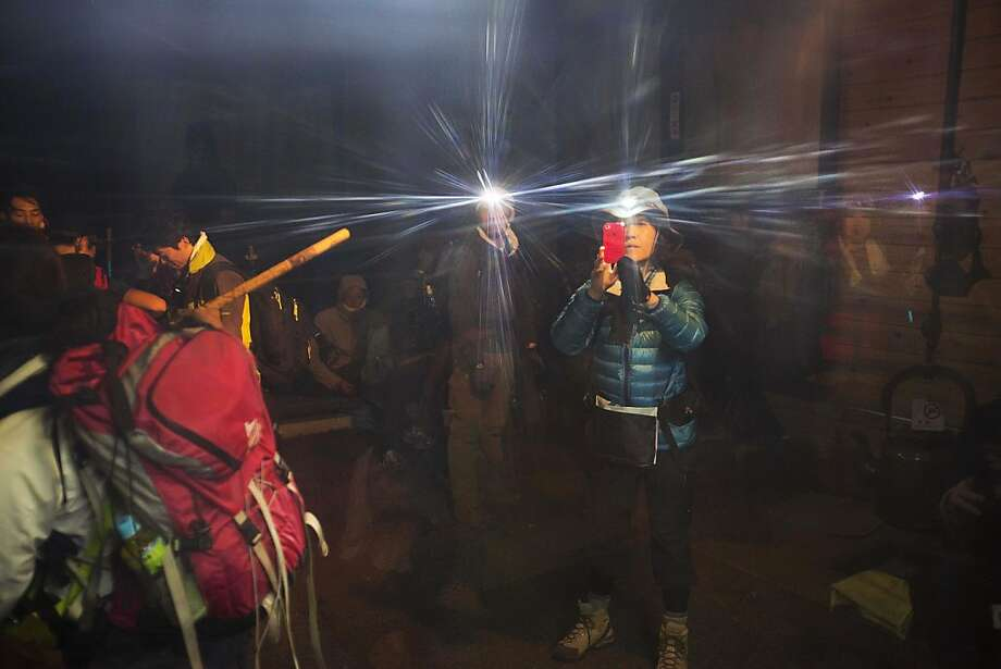 Hikers with headlamps stop to take pictures during their climb to the summit of Mount Fuji in Japan before dawn onSaturday, Aug. 10, 2013. Photo: David Guttenfelder, Associated Press