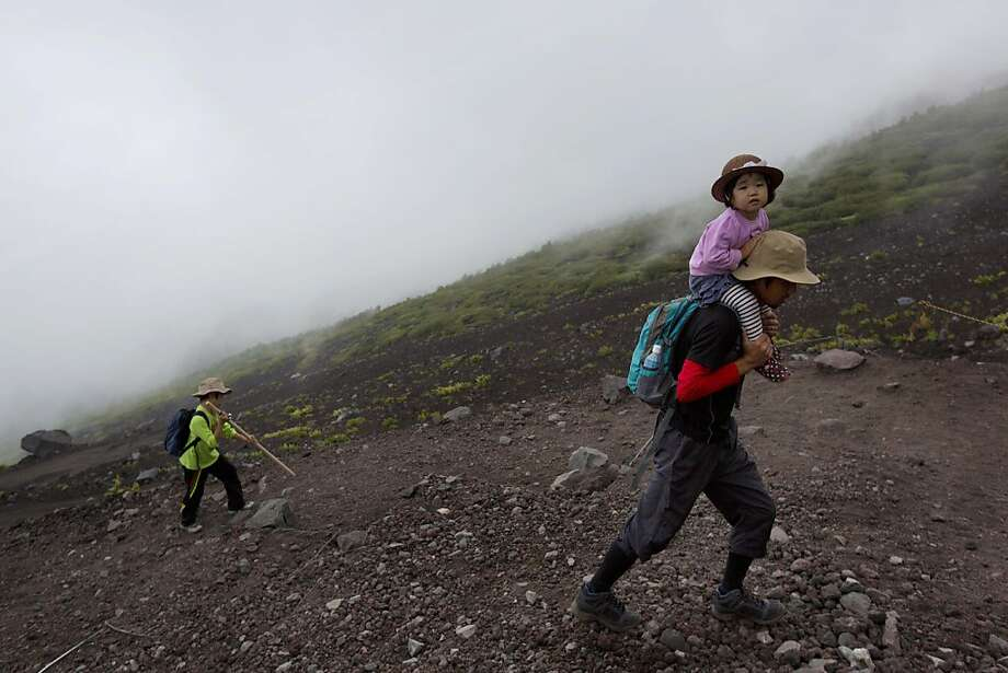A Japanese man and his children climb one of the trails on Mount Fuji, Aug. 10, 2013. Photo: David Guttenfelder, Associated Press