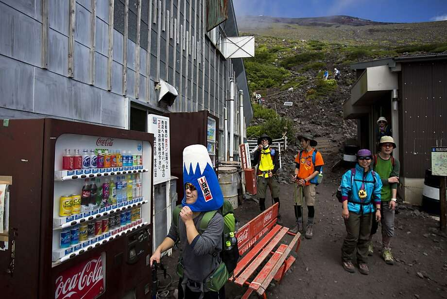 A Japanese man, wearing a Mount Fuji-shaped hat, passes by vending machines and benches at a rest station on one of the trails on Mount Fuji on Aug. 29, 2013. Photo: David Guttenfelder, Associated Press