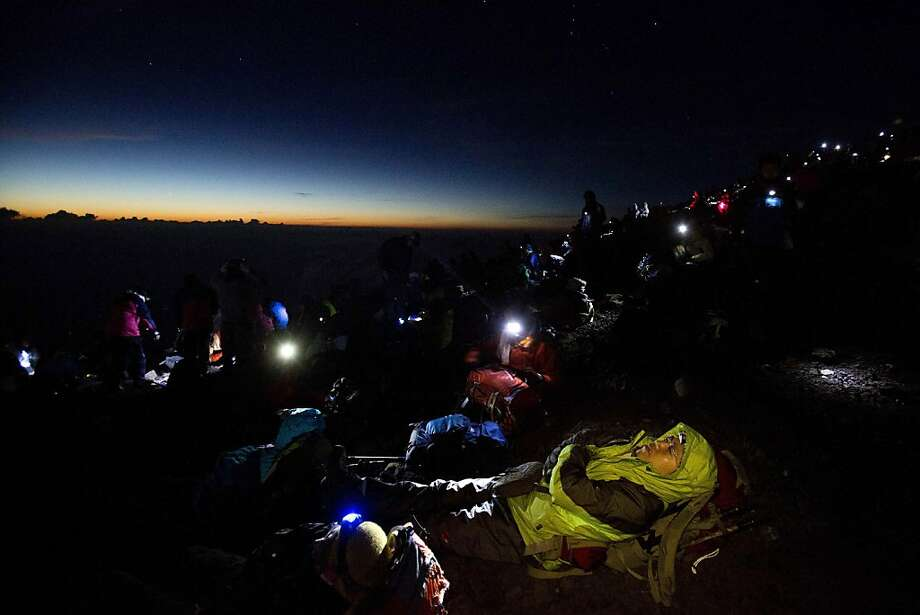 Thousands of hikers wait for the sun to rise on the summit of Mount Fuji before dawn on Aug. 11, 2013 photo. Photo: David Guttenfelder, Associated Press