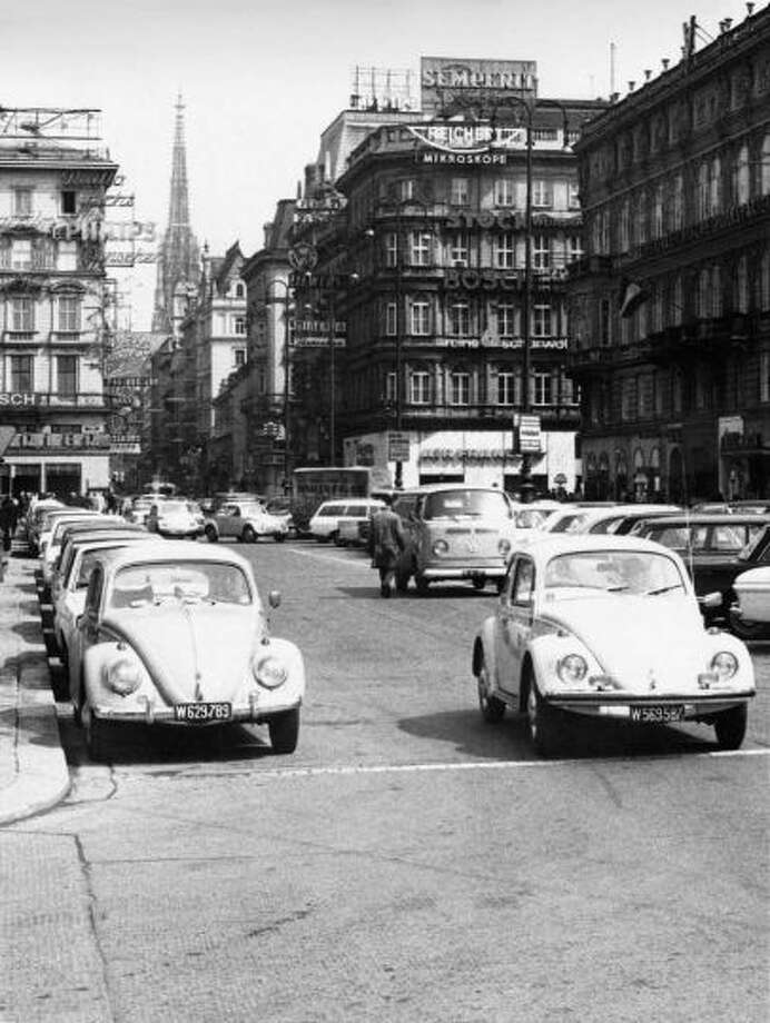 A Volkswagen Type 2 van putters along in the background behind Volkswagen Type 1 cars (aka Beetles) in Vienna, Austria, 1965. Photo: Hans Chr. R., Wikimedia Commons