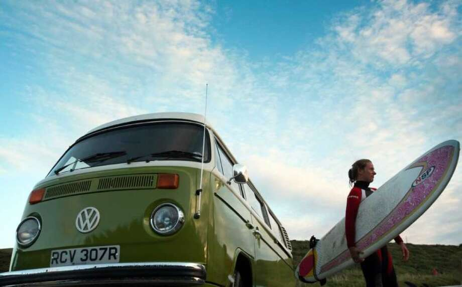 A female surfer stands by a Volkswagen camper van at Watergate Bay close to the Ripcurl Boardmasters at Fistral Beach on August 8, 2007 in Cornwall, England. Photo: Matt Cardy, Getty Images