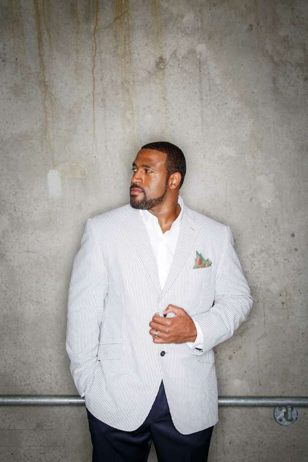 Houston Texans' football player Duane Brown poses for a photo at Reliant Stadium, Sunday, Aug. 18, 2013, in Houston.  Duane Brown has shed his once baggy look for more tailored pieces, like this seersucker jacket, shirt and slacks by designer Waraire Boswell with a pair of Cole Haan lace ups.   ( Michael Paulsen / Houston Chronicle ) Photo: Michael Paulsen, Staff / © 2013 Houston Chronicle