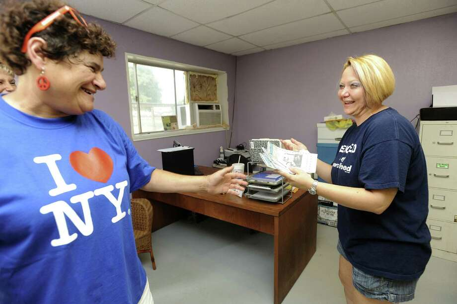 Lisa Morris of The Be Nice Club and the Be Nice Express, left, hands donated gift cards to Angie Gilstrap, president of the Canyon Lake Animal Shelter on Friday. The underlying aim of Morris' enterprise is to promote good will and cooperation. Photo: Billy Calzada / San Antonio Express-News