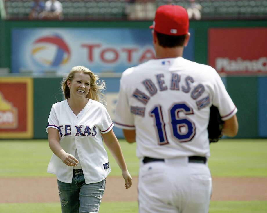 Texas Rangers first base coach Dave Anderson (16) greets former United States Army soldier Jessica Lynch after throwing out the ceremonial first pitch at Rangers Ballpark in Arlington, Texas, on Wednesday, September 11, 2013. (Jim Cowsert/Fort Worth Star-Telegram/MCT) Photo: Jim Cowsert, McClatchy-Tribune News Service / Fort Worth Star-Telegram