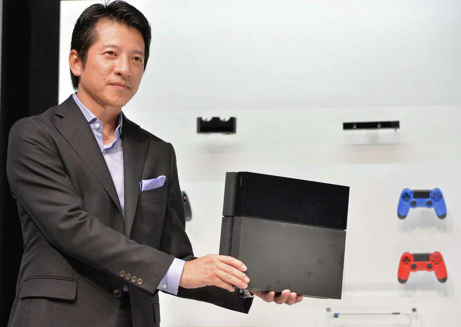 Hiroshi Kawano, President of Sony Computer Entertainment Japan Asia (SCEJA), displays the company's PlayStation 4 home gaming console during the SCEJA press conference in Tokyo on September 9, 2013. Sony said it will start selling its PlayStation 4 on February 22, 2014 in Japan, with a price tag of 420 USD (41,979 yen).   AFP PHOTO / KAZUHIRO NOGIKAZUHIRO NOGI/AFP/Getty Images Photo: KAZUHIRO NOGI / AFP