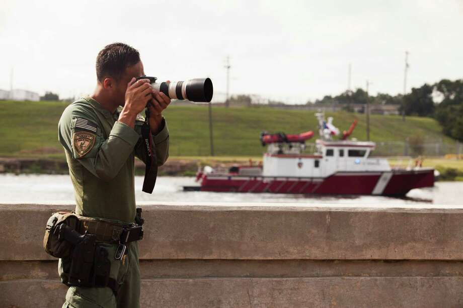 An officer who asked to remain unidentified in the HCSO's high risk operations unit takes photos with a camera usually used for surveillance as deputies show their physical assets during a visual demonstration of preparedness Sept. 11, 2013 in Houston at the Houston Ship Channel turning basin. Photo: Eric Kayne, For The Chronicle / ©Eric Kayne 2013
