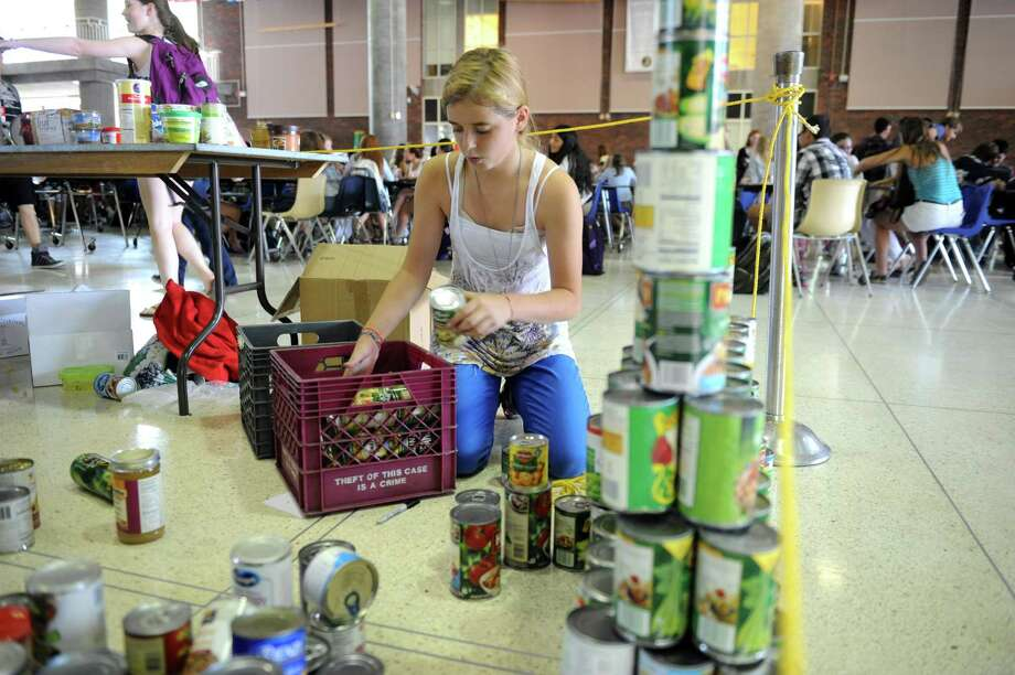 Olivia Horton, 14, freshmen, put cans away at Greenwich High School's canned food drive in Greenwich, in Conn., Wednesday, Sept. 11, 2013. Greenwich High School students volunteering in the school's One-For-One On Nine-One-One food drive show items donated for the initiative. Photo: Helen Neafsey / Greenwich Time