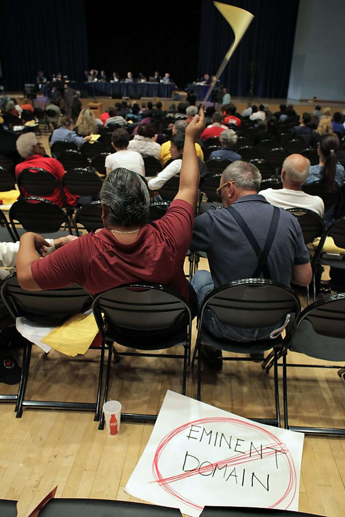 A supporter of the eminent domain measure waves a flag as a sign urging rejection by the council lies on the floor.